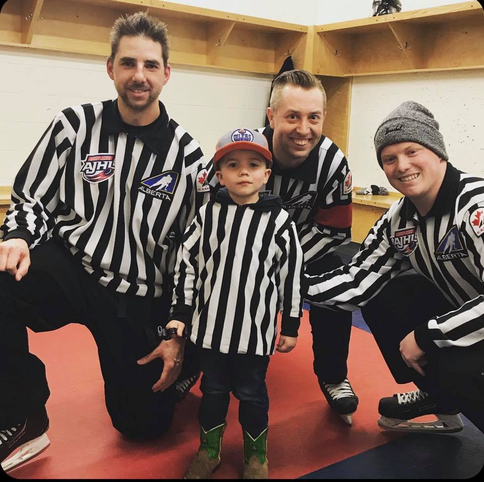 Brad Holfeld, Danny Gadowski, and Brent Young meet a young fan at an AJHL game